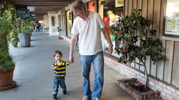 man and boy walking at carlmont village shopping center